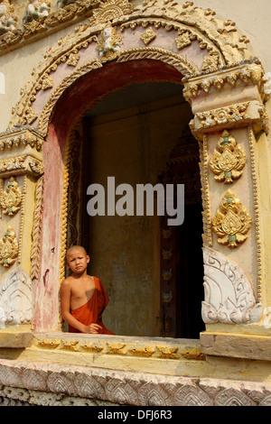 Monk en porte, Luang Prabang, Patrimoine Mondial de l'UNESCO, le Laos, l'Indochine Banque D'Images