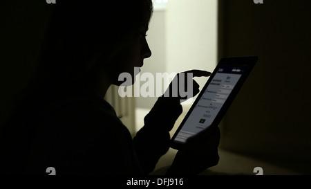 Silhouette d'une jeune fille à l'aide d'une tablette numérique sur facebook page. Banque D'Images
