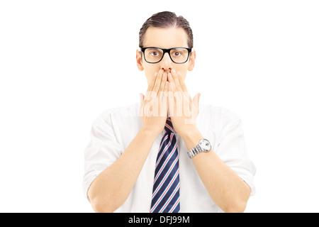 Jeune homme avec les mains sur sa bouche, stupéfaite et sans voix Banque D'Images