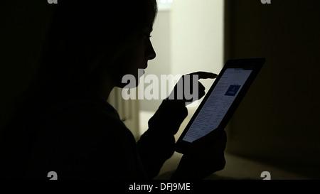 Silhouette d'une jeune fille à l'aide d'une tablette numérique avec une porte ouverte. Banque D'Images