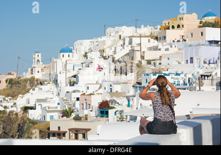 Santorin (thira), CYCLADES, en Grèce. Un vacancier photographier le pittoresque village de falaise d'Imerovighli Banque D'Images