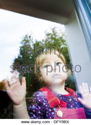 Enfant derrière une vitre à la triste Banque D'Images