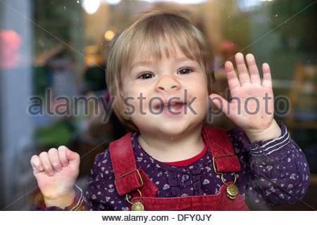 Enfant derrière un volet de fenêtre Banque D'Images