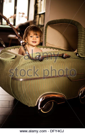 Jeune fille dans une voiture ancienne en osier en forme de Landau le 50. Banque D'Images