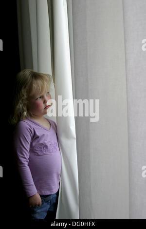 Jeune fille sérieuse de peering out window Banque D'Images