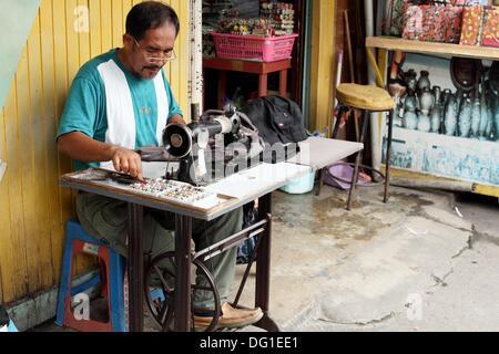 Tailer assis à la machine à coudre dans son atelier, Kota Kinabalu, Sabah, Malaisie, Bornéo Banque D'Images