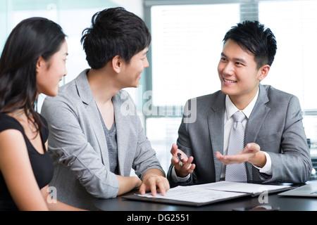 Jeune couple avec le consultant financier Banque D'Images