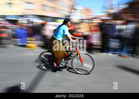 El Alto, en Bolivie. 12 octobre, 2013. Un coureur monte comme spectateurs passé elle prend part à une course cycliste Banque D'Images