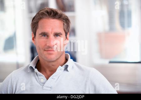 Homme assis sur le canapé de détente à la maison à la caméra à Smiling