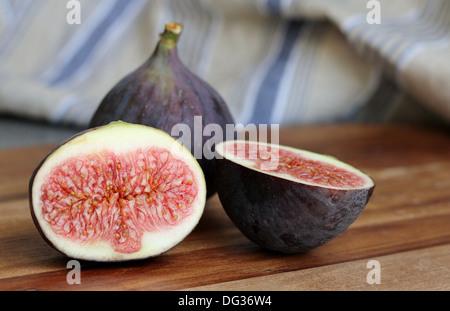 Figues fraîches coupées sur une cuisine en bois, avec des rayures bleu , dans l'arrière-plan, profondeur de champ Banque D'Images