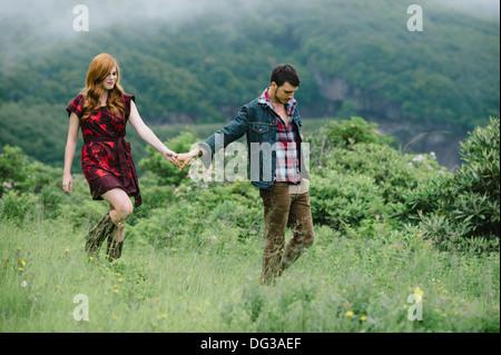 Young Couple Holding Hands tout en marchant à travers champs Banque D'Images