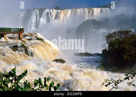 Le Brésil, le Parc National d'Iguaçu: touristes sur plate-forme d'observation appréciant l'énorme volume d'eau, Banque D'Images