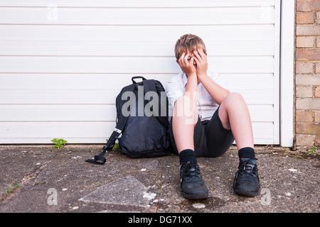 Un garçon de 10 à la triste et déprimé dans son uniforme de l'école montrant les effets de l'intimidation au Royaume Banque D'Images