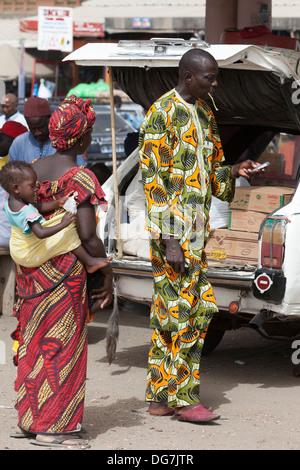 Sénégal, Saint Louis. Vêtements africains colorés à la station de bus et taxi. L'homme est à l'aide d'un stick à Banque D'Images