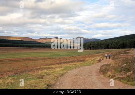 Le but de Glen Muick avec deux promeneurs sur le chemin d'Loch Muick, Aberdeenshire, Ecosse, Royaume-Uni. Banque D'Images