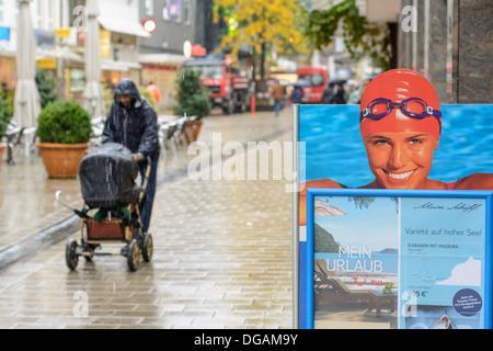 Affiche publicitaire montre jolie femme avec bonnet de bain et des lunettes de natation et le père avec bébé buggy Banque D'Images
