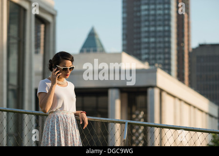 Mid adult women using mobile phone, Manhattan, New York Banque D'Images
