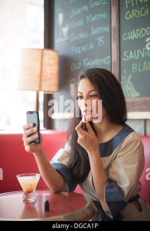 Mid adult women using mobile phone pour appliquer le rouge à lèvres dans le Banque D'Images