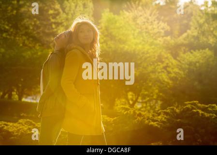 Deux jeunes femmes se tenant debout dos à dos dans park Banque D'Images