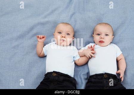 Portrait de deux garçons de bébé tenant la main sur couverture bleue, overhead view Banque D'Images