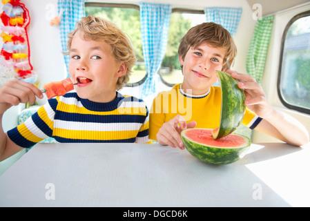 Les garçons eating watermelon en caravane, portrait Banque D'Images