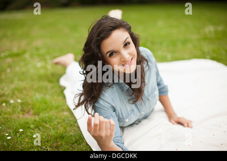 Young woman lying in park smiling, portrait Banque D'Images