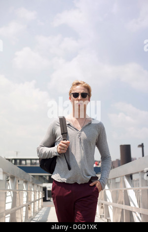 Jeune homme marchant sur la passerelle, Brooklyn, New York City, USA Banque D'Images