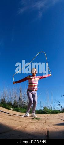 Une jeune fille passe une corde. Banque D'Images