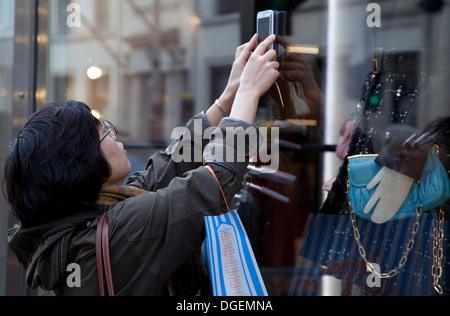 Jeune femme photographies touristiques fashion store display à New Bond Street, London using smartphone