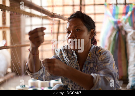Une femme travaille dans un petit village à l'extérieur de l'usine textile de Phnom Penh, Cambodge. Photos © Dennis Banque D'Images