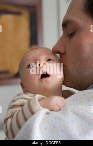 Mid adult father kissing baby boy Banque D'Images