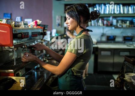 Teenage serveuse préparer le café en cuisine cafe Banque D'Images