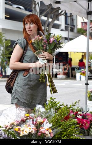 Mid adult woman l'achat de fleurs dans la ville de décrochage Banque D'Images