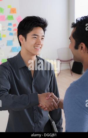 Les employés de bureau masculins shaking hands
