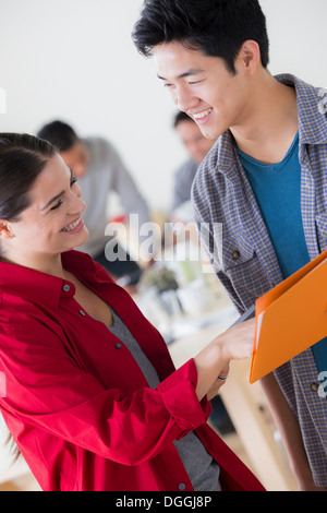 Young man and woman chatting in office Banque D'Images