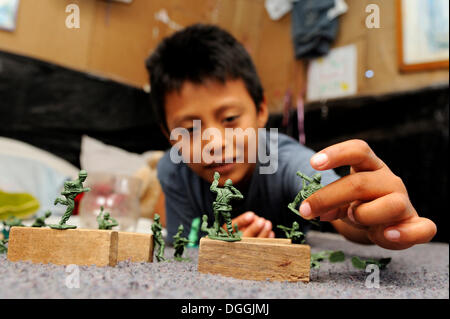 Boy Playing with toy soldiers en plastique, dans un quartier pauvre de Cancun, péninsule du Yucatan, Quintana Roo, Banque D'Images