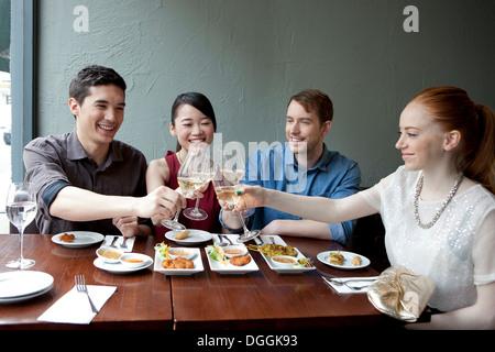 Quatre amis toasting white wine in restaurant Banque D'Images