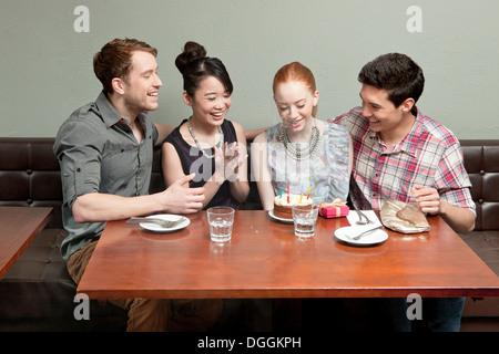 Quatre amis celebrating birthday in restaurant Banque D'Images