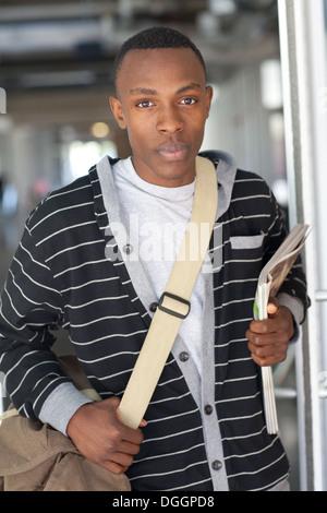 Dix-huit ans college student walking en classe avec messenger bag et de revues. Banque D'Images