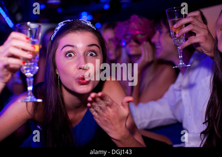 Young woman blowing kiss in limousine Banque D'Images