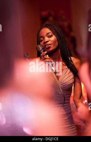 Jeune femme chantant avec microphone Banque D'Images
