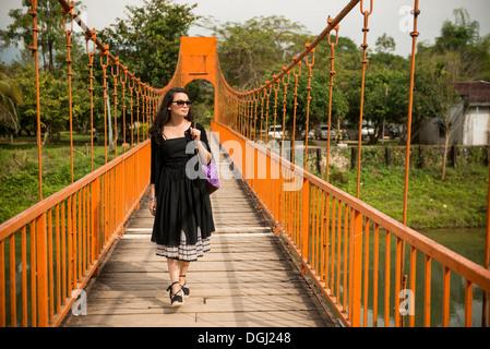 Femme sur pont sur la rivière, Vang Vieng, Laos Banque D'Images