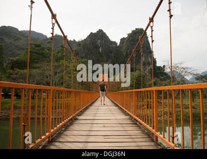 L'homme sur pont sur la rivière, Vang Vieng, Laos Banque D'Images