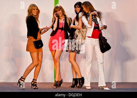 Quatre modèles féminins d'effectuer avec les téléphones mobiles sur une scène Banque D'Images