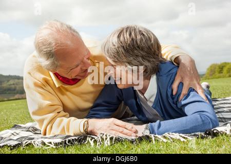 Mari et femme lying on stomach on blanket in field