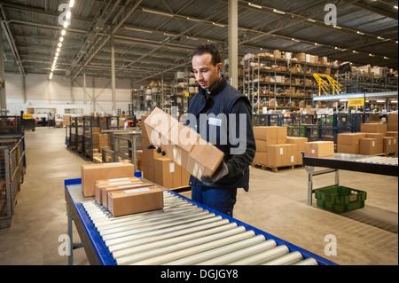 Homme employé de l'entrepôt la sélection de boîtes de carton à partir de la courroie du convoyeur Banque D'Images