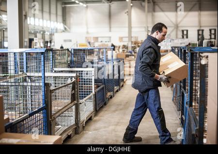 Male warehouse worker lifting boîte carton sur chariot distributeur Banque D'Images