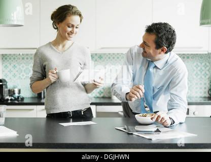 Mid adult woman reading document pendant le petit-déjeuner avec mari Banque D'Images