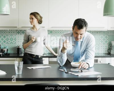 Mature businessman using tablet pendant le petit-déjeuner dans la cuisine Banque D'Images
