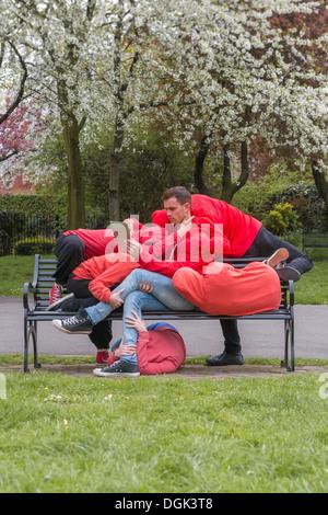 Groupe de jeunes effectuant sur banc de parc de la ville Banque D'Images